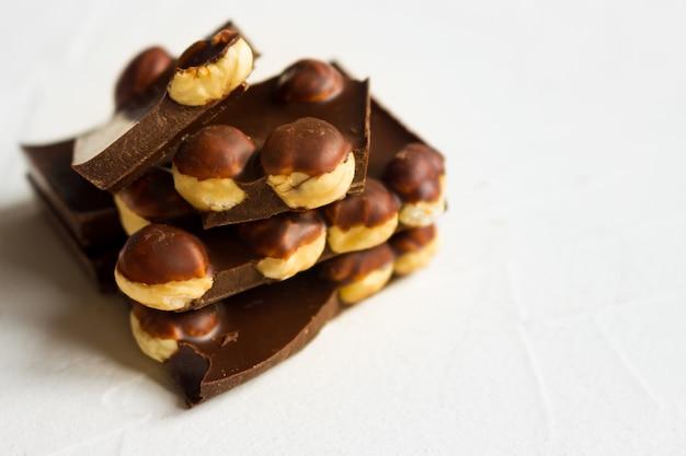Torre di pezzi di cioccolato fondente nocciola su sfondo bianco.