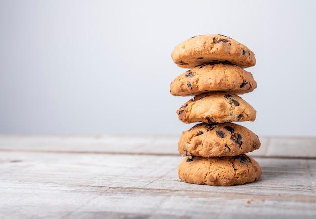 Torre dorata del biscotto con pezzi di cioccolato su fondo di legno