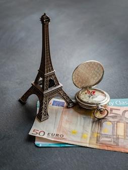 Torre eiffel con banconota da 50 euro e carta d'imbarco