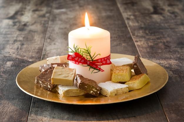 Torrone di natale e candela bianca sulla tabella di legno