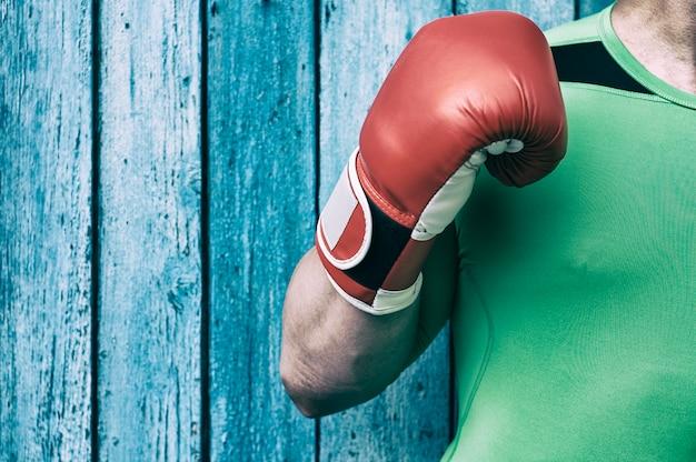 Torso di un uomo e un braccio destro in guanti da boxe rossi