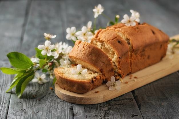 Torta a fette con uvetta decorata con un ramo con fiori di ciliegio sul tavolo. deliziose torte fatte in casa.