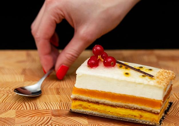 Torta a più strati con crema di aria e ribes rosso su un fondo di legno, cucchiaino