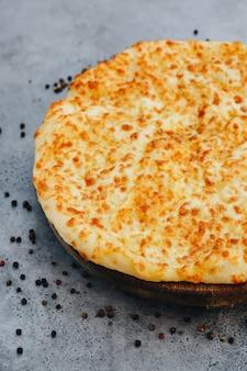 Torta affettata con formaggio su una tavola di legno su sfondo grigio. khachapuri