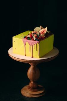 Torta agli agrumi gialla decorata con fichi, lamponi, mirtilli e limone.
