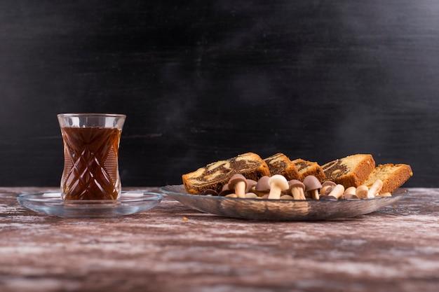 Torta al cacao con cialde e biscotti in un piatto di vetro con un bicchiere di tè