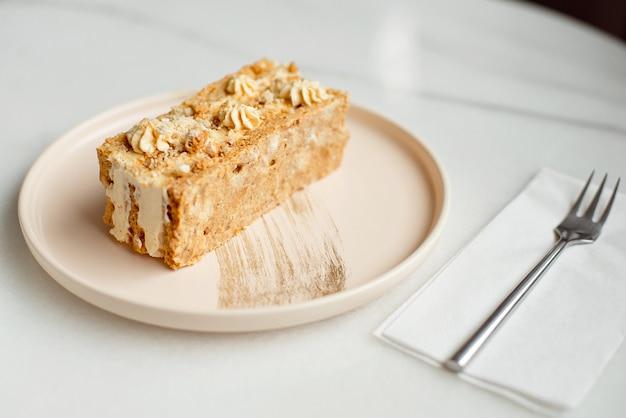 Torta al caffè. un pezzo di torta su un piatto. dessert dolce su un rosa rotondo con un fondo di legno del piatto. avvicinamento