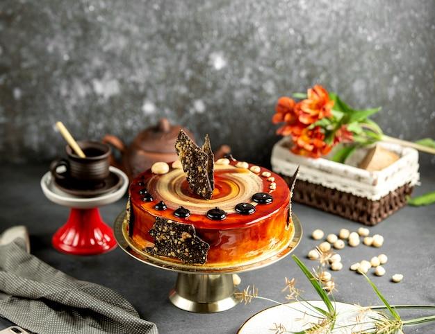 Torta al caramello con decorazioni di cioccolato e noci