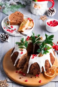 Torta al cioccolato a fette di natale con glassa bianca, rami di agrifoglio e chicchi di melograno in legno grigio