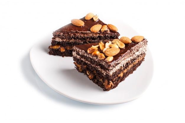 Torta al cioccolato con caramello, arachidi e mandorle isolati su uno sfondo bianco.