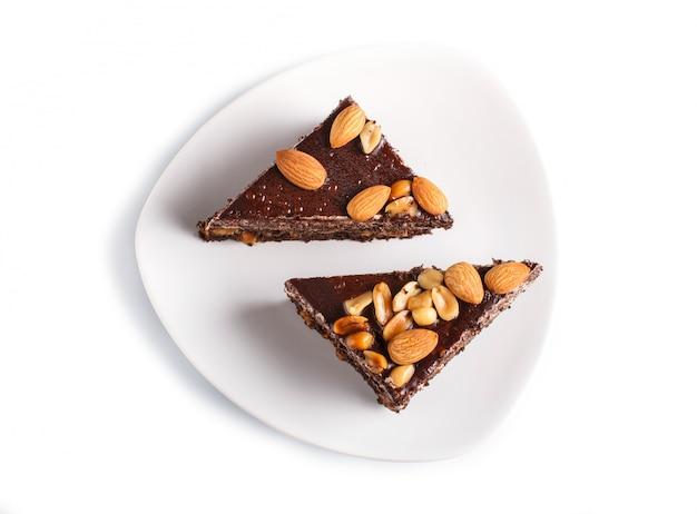 Torta al cioccolato con caramello, arachidi e mandorle isolato su una superficie bianca.