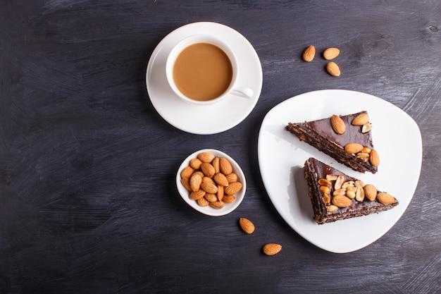 Torta al cioccolato con caramello, arachidi e mandorle su un legno nero.