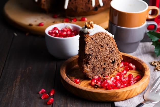 Torta al cioccolato con clic di natale con glassa bianca e chicchi di melograno su un legno scuro, tazze e decorazioni,