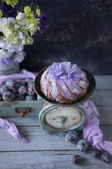Torta al cioccolato con fiori lilla e prugne in una scatola di legno d'epoca