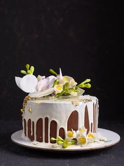 Torta al cioccolato decorata con fiori e glassa bianca versata. copyspace