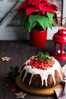 Torta al cioccolato di natale con glassa bianca e chicchi di melograno un legno scuro con lanterna rossa e stella di natale