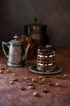 Torta al cioccolato e caffettiera vintage. gocce di cioccolato e chicchi di caffè
