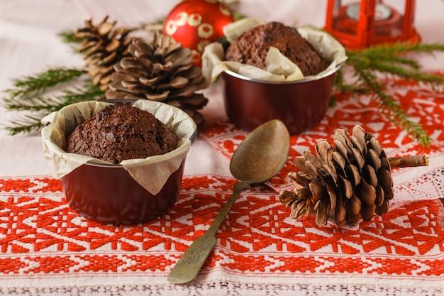 Torta al cioccolato e piccoli cupcakes con decorazioni sul tavolo rustico