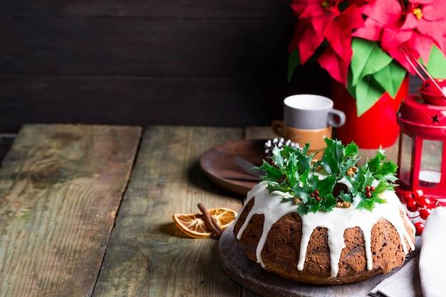 Torta al cioccolato fondente di natale decorata con glassa bianca e rami di bacche di agrifoglio con lanterna rossa un legno scuro