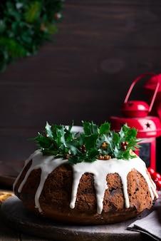 Torta al cioccolato fondente di natale decorata con glassa bianca e rami di bacche di agrifoglio con lattern rosso su un legno scuro