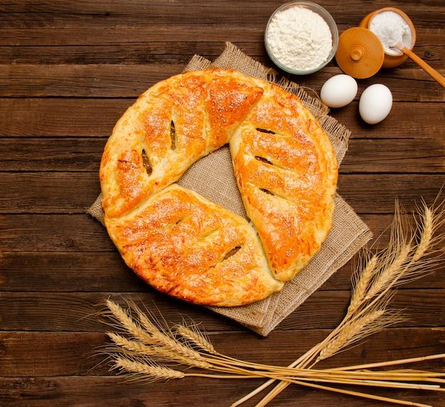 Torta al licenziamento, ingredienti per la cottura, spighe di grano su fondo di legno.