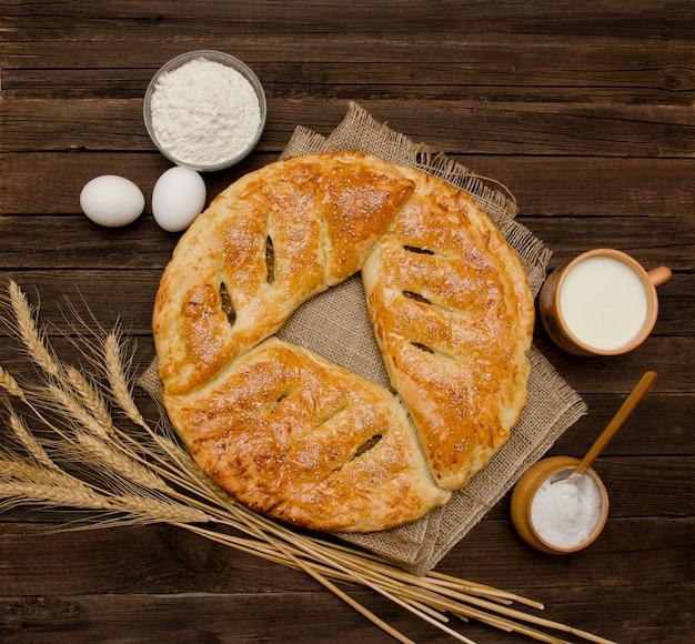 Torta al licenziamento, tazza di latte, ingredienti per la cottura, spighe di grano su fondo di legno.