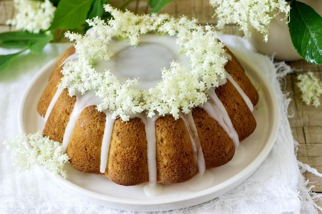Torta al limone con glassa di zucchero e sciroppo di sambuco, decorata con fiori di sambuco. stile rustico.