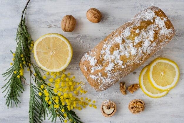 Torta al limone con noci su una superficie bianca in legno, un ramoscello di fiori di mimosa