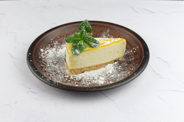 Torta al limone mascarpone cheesecake con foglia di menta su uno sfondo bianco
