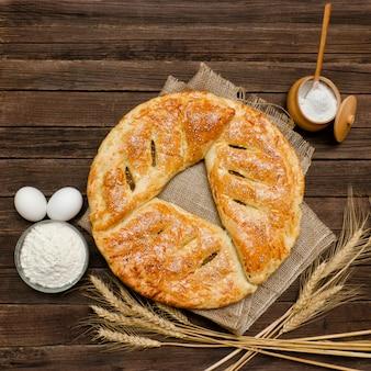 Torta al sacco, ingredienti per la cottura. spighe di grano su fondo in legno.