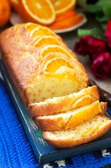 Torta all'arancia, decorata con fettine di arancia su uno sfondo di arance succose e un mazzo di tulipani. stile rustico.