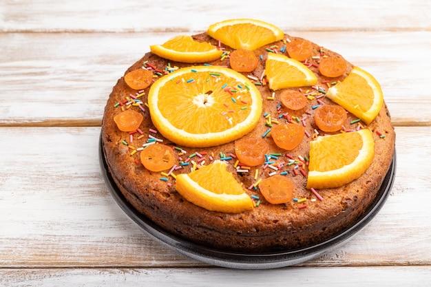 Torta all'arancia su una tavola di legno bianca. vista laterale, da vicino
