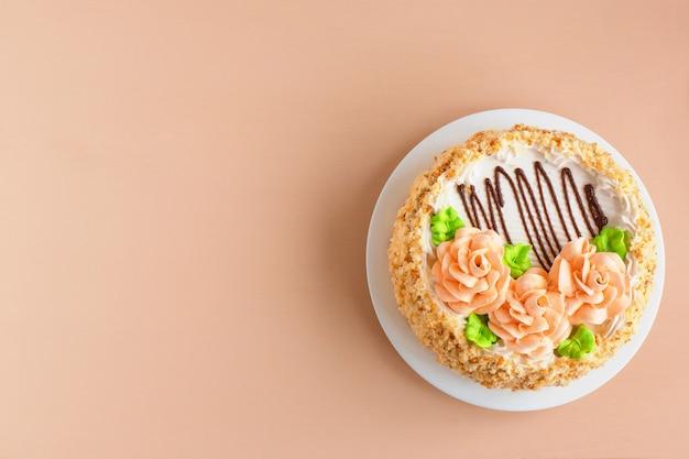 Torta alla crema di biscotti con rose cremose sul piatto bianco