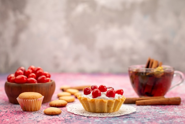 Torta alla crema di vista frontale con mirtilli rossi freschi insieme a biscotti alla cannella e tè sul tè dolce del biscotto luminoso della scrivania