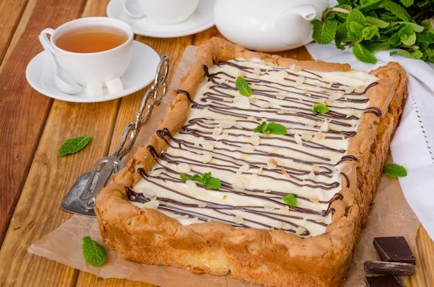 Torta alla crema fatta in casa con crema pasticcera e crema bavarese con glassa al cioccolato, petali di mandorle e foglie di menta in cima su una superficie di legno scuro