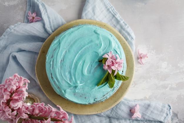 Torta alla moda blu con fiori e menta sulla scatola di legno. copia spazio, vista dall'alto, cibo piatto laico