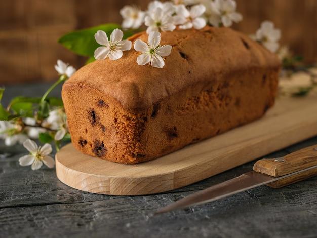 Torta appena sfornata con uvetta in fiori di ciliegio su un tavolo di legno. deliziose torte fatte in casa.
