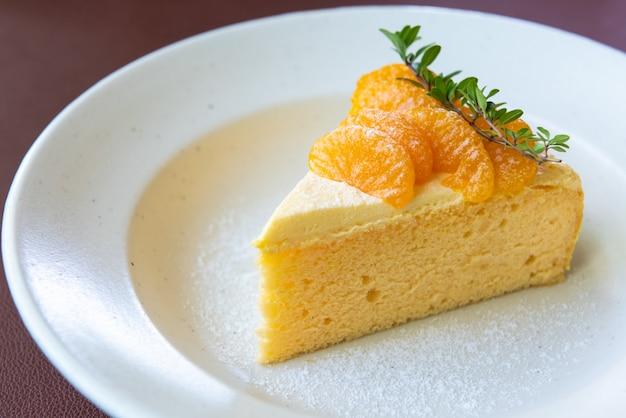 Torta arancione con la guarnizione arancione della frutta sul piatto bianco