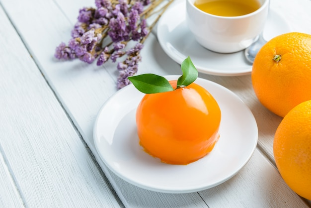 Torta arancione sulla tavola di legno bianca