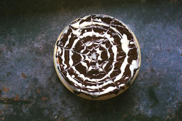 Torta artigianale di zucca, cioccolato bianco e nero. ragnatela e concetto di halloween.