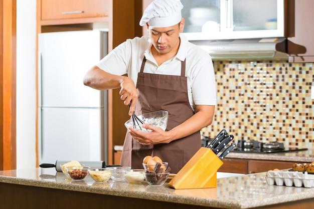 Torta asiatica di cottura dell'uomo in cucina domestica