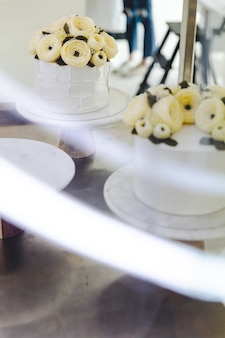 Torta bianca con fiori di crema di burro decorata su supporto con scia luminosa in primo piano.