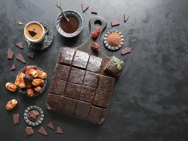 Torta brownie al cioccolato con caffè nero, dessert sul tavolo nero