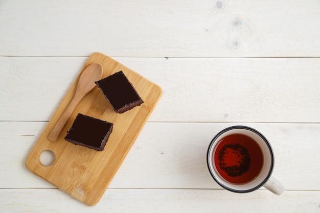 Torta brownie su un vassoio di bambù con una tazza di tè su uno sfondo bianco in legno con spazio per il testo