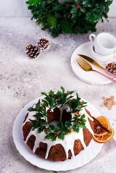 Torta bundt al cioccolato fondente di natale decorata con glassa bianca e rami di bacche di agrifoglio su un cemento chiaro