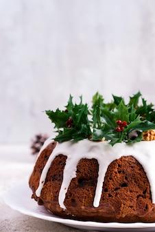 Torta bundt al cioccolato fondente di natale decorato con glassa bianca e rami di bacche di agrifoglio close-up