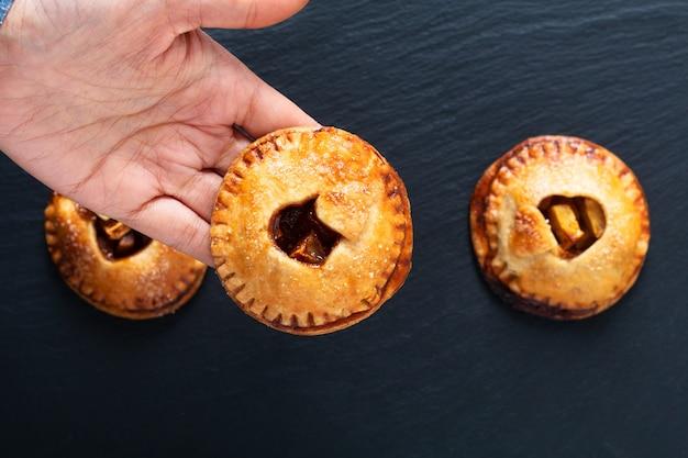 Torta casalinga al forno fresca della mano della cannella della mela di concetto di idea del biglietto di s. valentino dell'alimento sul nero