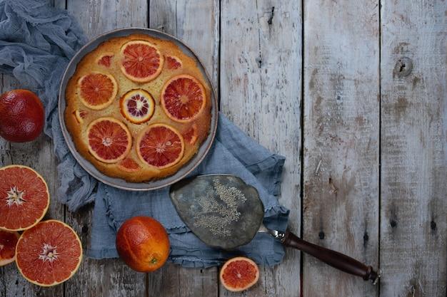 Torta casalinga con arance rosse sul tavolo in legno chiaro. spatola torta vintage