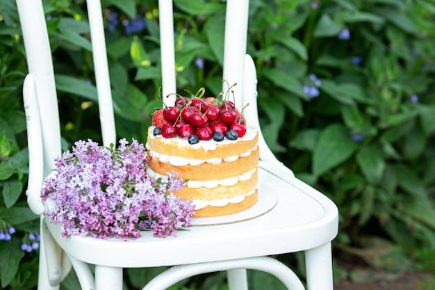 Torta casalinga del biscotto di estate con crema e le bacche fresche in sedia nel giardino