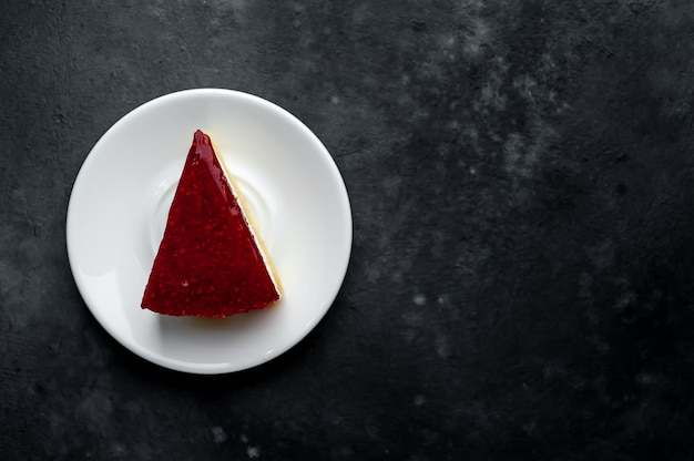 Torta cheesecake con lamponi su un piattino bianco su uno sfondo di pietra